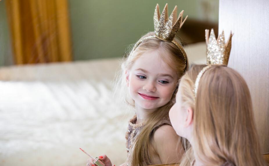 FOKUS PÅ UTSEENDE: En jente med prinsessekrone ser seg selv i speilet. Dora Thorhallsdottir mener mange jenter man tar med seg skjønnehtsfokuset fra ung alder og videre gjennom livet.