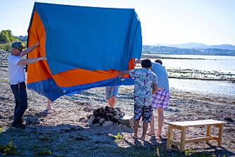 Plassere teltet. Etter at flammene er slukket og glørne gravd ut, klipper du hull i bunnen på teltet og setter det over steinovnen.