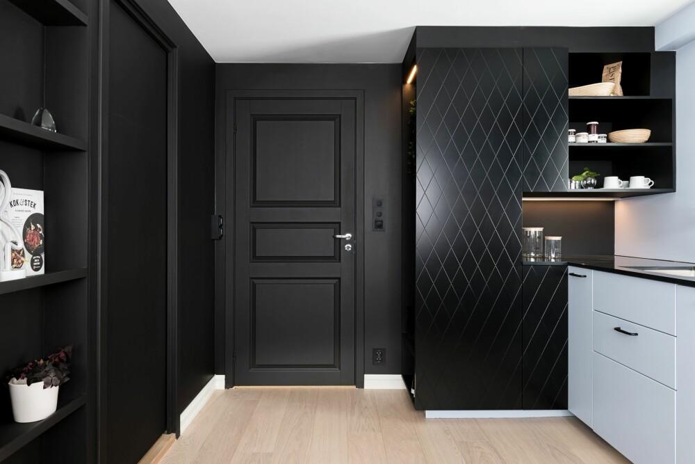 MØRKE OG LYSE FARGER: Inngangssonen er holdt i svart, hvilket fører til at dører og hyller går mer i ett med veggene, og skaper et rolig inntrykk. Skyvedøren til venstre leder inn til et slags walk-through-closet som igjen fører til et lite bad.