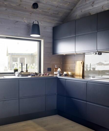 STORT VINDU: I stedet for overskap har familien prioritert et stort vindu over kjøkkenbenken. Lampe fra Ellos. Kjøkken fra Aubo og Monter, type Venezia, malt i dempet sort.