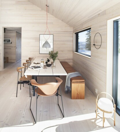 SPISEPLASS: Her står et selvlaget bord av rester av Dinesen Douglas plank, som også er brukt til gulvet, understellet er i svart ask. Benken er også laget av Dinesen-gulvet, og en skinnpute sydd på mål gjør det behagelig å sitte lenge. Skinnet er Old english tan leather levert av Love Leather UK. Spisestuestolene er CH88, design Hans Wegner, i oljet, røkt eik med svart pulverlakkert understell, produsent er Carl Hansen. Den brune stolen er Masculo dining chair fra Gubi. Lampen er Heavy Pendant, design Benjamin Hupert for Decode London. På gulvet står Miguel Milas lampe Cesta fra Santa & Cole. Kopper og tekanne fra Bolina.
