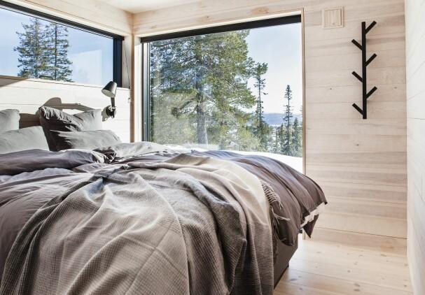 SOVEROM: På soverommet kommer naturen tett på, takket være vinduer som går fra gulv til tak. Den svarte knaggen er fra Ikea. Sengetøyet er fra Beach House Company, sengeteppet er fra Elvang og taklampene heter Cult og er fra Nordlux.