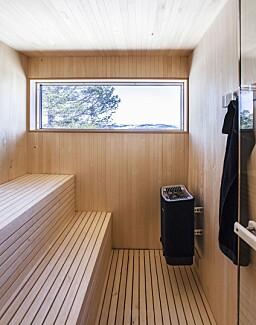BADSTU: Innenfor badet er det bygget badstu i ospepanel og spiler. Også her kan man nyte nærhet til naturen, takket være vinduet i enden av rommet. Døren inn er en badstudør fra Tylö DGL med klart glass og karmer i kvistfri, lys osp som matcher panelet og spilene.