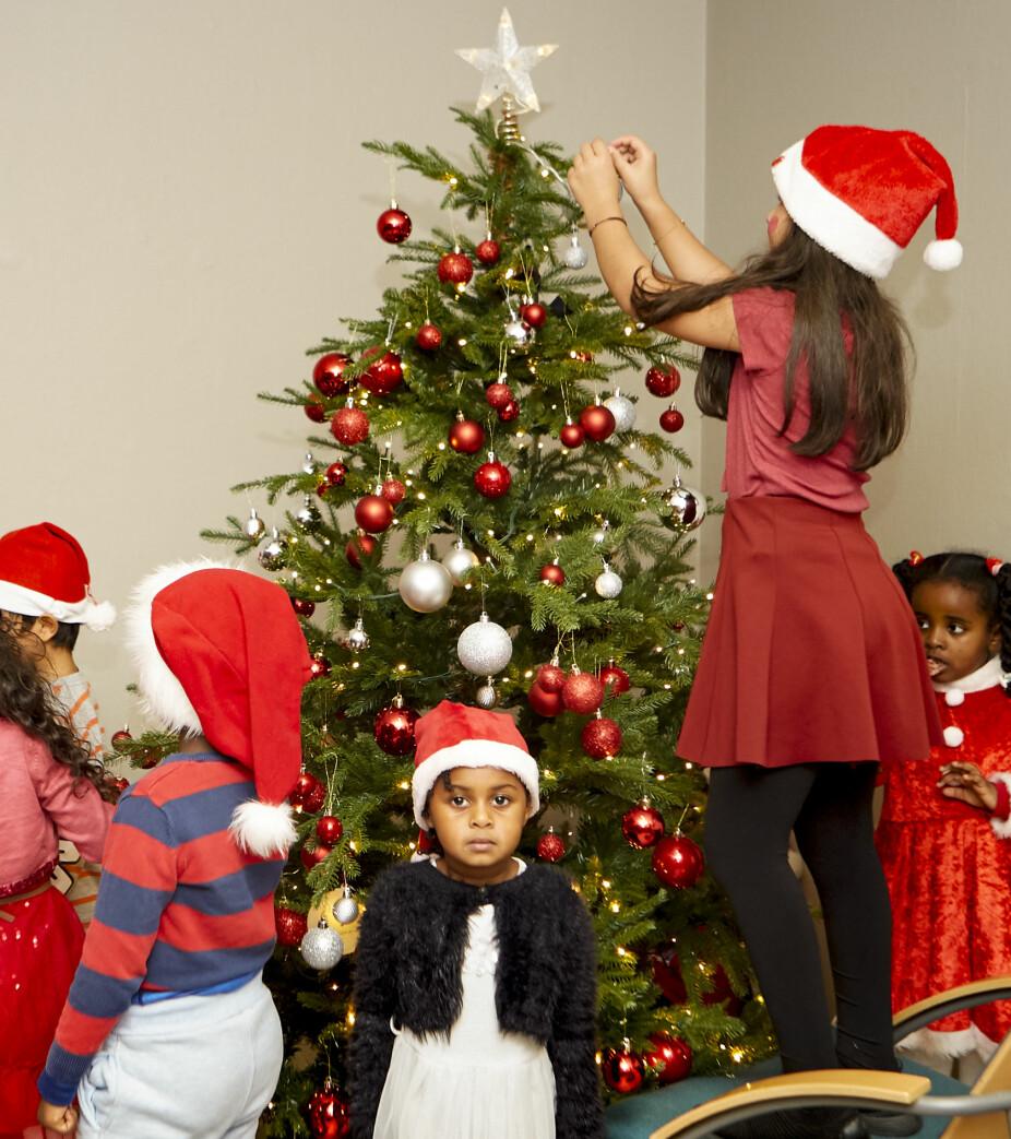 <b>PYNTEGLEDE:</b> Det kravlet ivrige barn over alt rundt treet, og de ga seg ikke før hver eneste gren var søkklastet med kuler. Haben (4) og Eliana (2) synes det er stas å bli med på bildet.