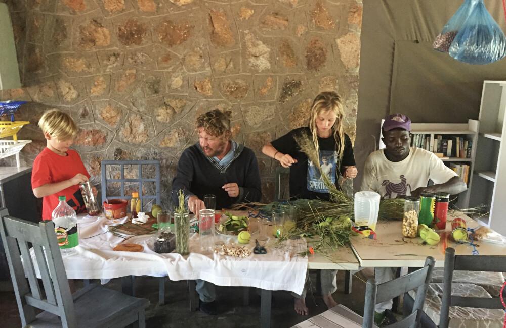 <b>LAGER LEKER:</b> Også små bavianer trenger nye utfordringer, og en del av arbeidet var å lage leker til dem. Her putter familien mat i tennisballer som kamufleres med gress, slik at bavianene kan lete etter dem.