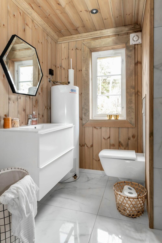 De badkamer heeft marmeren tegels op de vloer, terwijl de muren een Twilight-kleur hebben van Tyrilin.  De gootsteenkast is van IKEA en de spiegel is gekocht bij komplet.no.