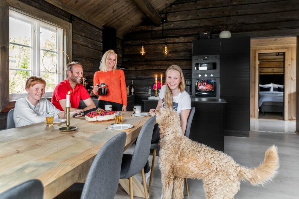 Dennis (fv), Ivar, Ranveig, Albertine en de hond Ulla verzamelen zich rond de zelfgemaakte eettafel van de stand.  Olivers jongste man was bij een vriend toen Hytteliv op bezoek was.