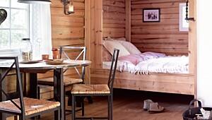 På denne hytta har de sengen på kjøkkenet